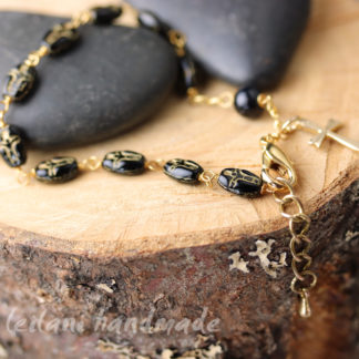 rosary bracelet with black and gold crucifix beads